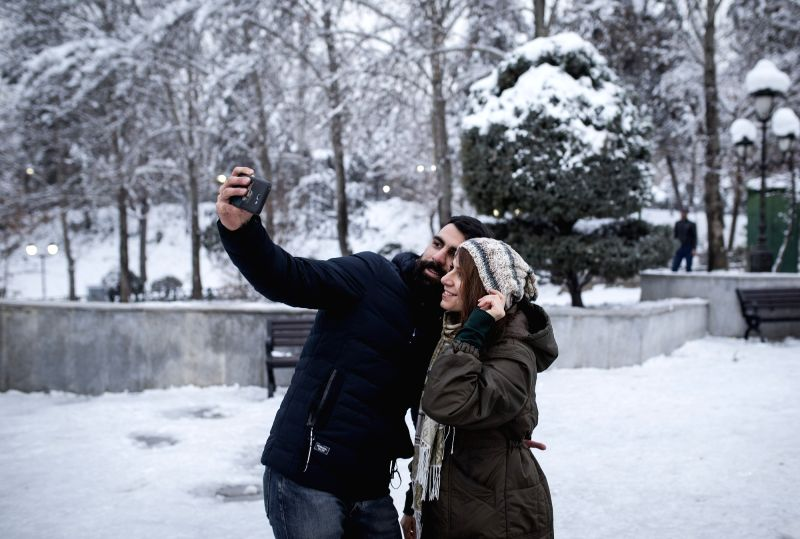 TEHRAN, Jan. 31, 2018 - People take selfie at a park after a snowfall in Tehran, capital of Iran, on Jan. 30, 2018.