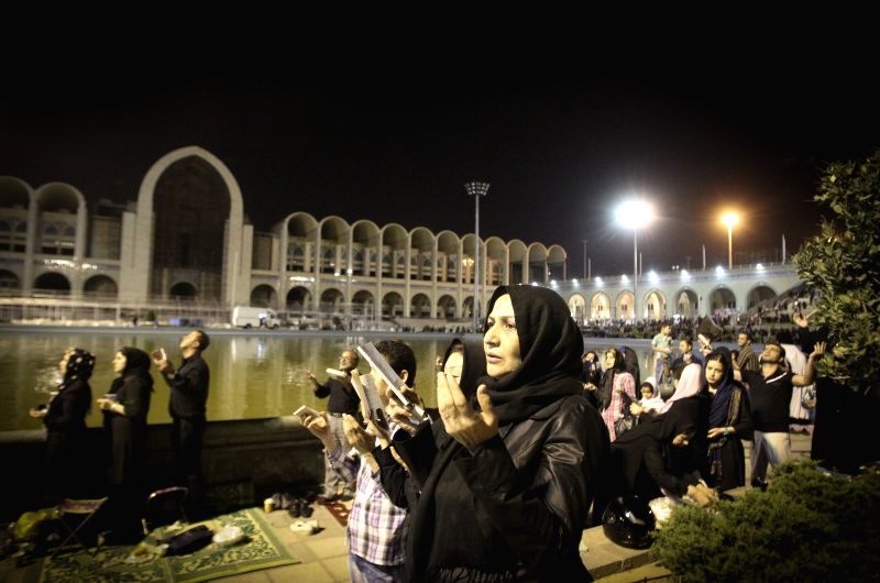 Iranian Shiite Muslims pray during a religious ceremony of the holy month of Ramadan at the Imam Khomeini grand mosque in Tehran, Iran, on July 21, 2014. ...