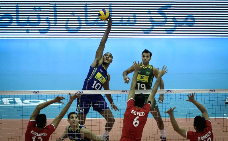 Ricardo Lucarelli (top) of Brazil spikes the ball during the match against Iran during FIVB Men's Volleyball World League 2014 in Tehran, capital of Iran, June 15, ..