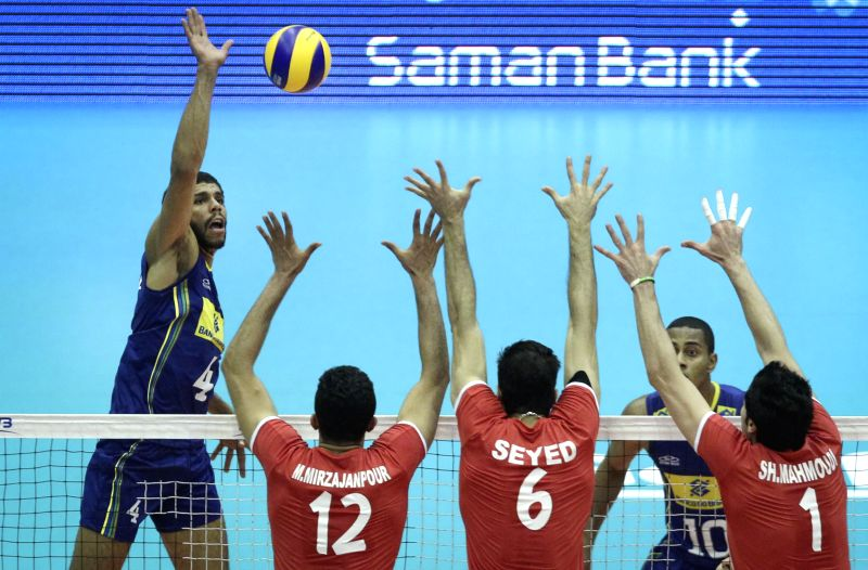Wallace De Souza (L) of Brazil spikes the ball during the match against Iran during FIVB Men's Volleyball World League 2014 in Tehran, capital of Iran, June 15, ...