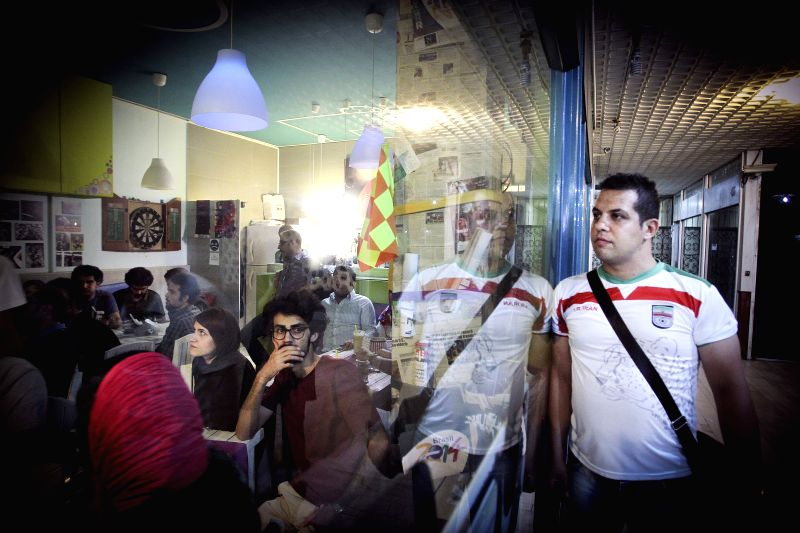 Iranian soccer fans react while watching the televised match between Iran and Nigeria at 2014 FIFA World Cup, in Tehran, capital of Iran, June 16, 2014. The match ...