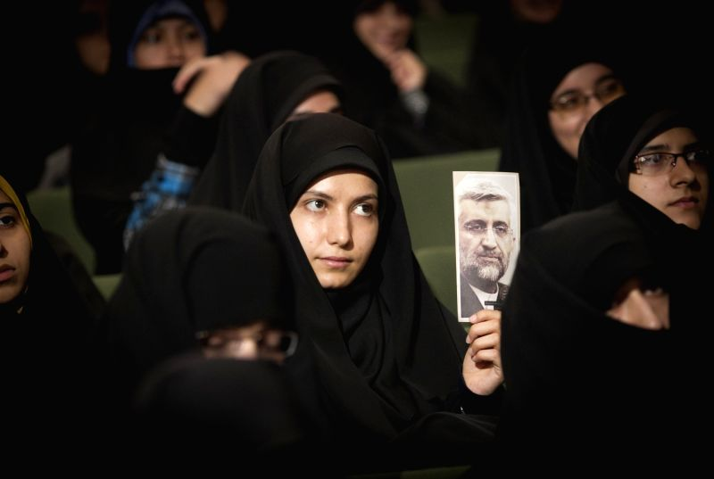 A woman raises a poster of Iran's chief nuclear negotiator and presidential candidate Saeed Jalili during a campaign rally at University of Tehran, Iran, on June