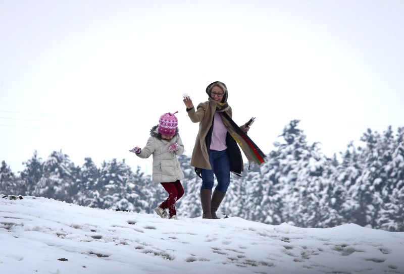 A woman and her daughter play with snow in northern Tehran, capital of Iran, on March 10, 2015. The first snowfall in 2015 hit Tehran on Tuesday. (Xinhua/Ahmad ...