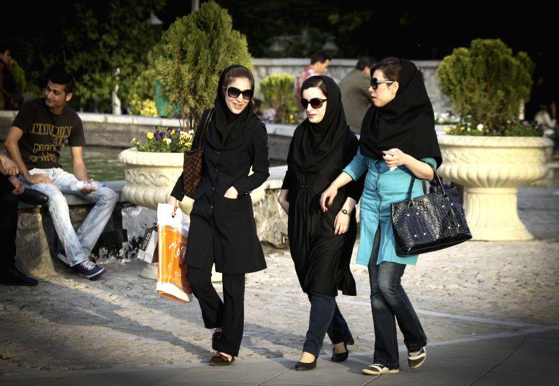Iranian women walk on a street in downtown Tehran, capital of Iran, on May 17, 2014. Iranian women enjoy lighter Hijab as the warm season approches. Hijab, a coverage