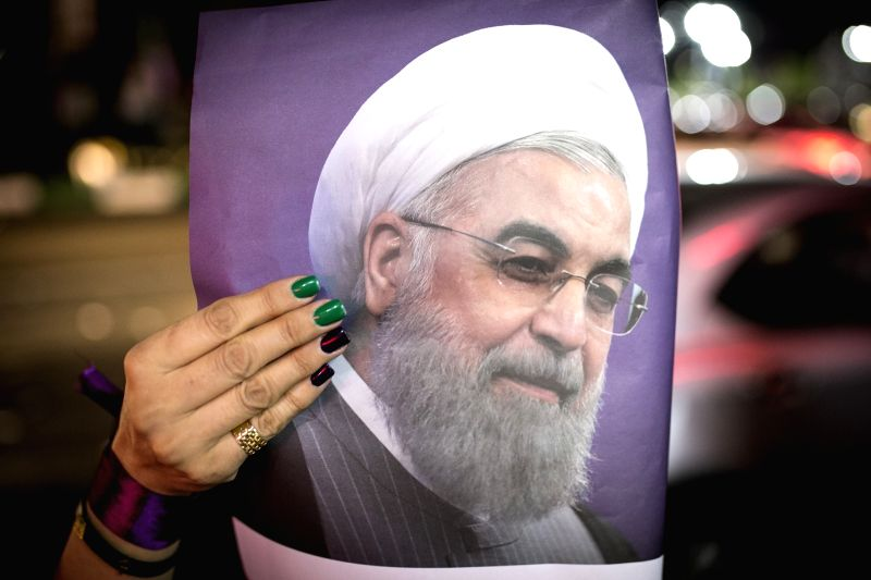 TEHRAN, May 18, 2017 - A supporter holds a poster of Iranian President and presidential candidate Hassan Rouhani during a street campaign in Tehran, Iran, May 18, 2017. Iran's 12th presidential ...