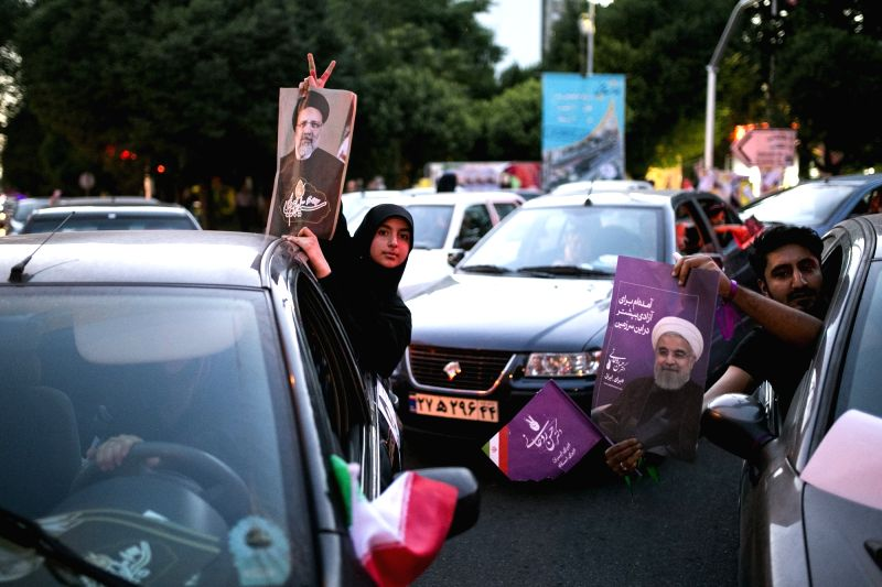 TEHRAN, May 18, 2017 - Supporters hold posters of presidential candidate Ebrahim Raisi (L) and President and presidential candidate Hassan Rouhani during a street campaign in Tehran, Iran, May 17, ...