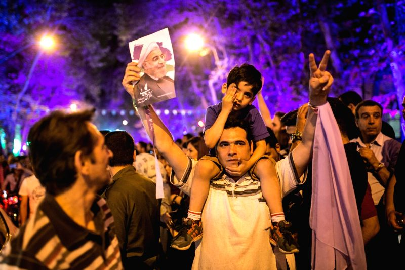 TEHRAN, May 21, 2017 - A supporter raises the poster of Iranian President Hassan Rouhani to celebrate his victory in the presidential election in Tehran, Iran, May 21, 2017. Iran's incumbent moderate ... - Hassan Rouhani