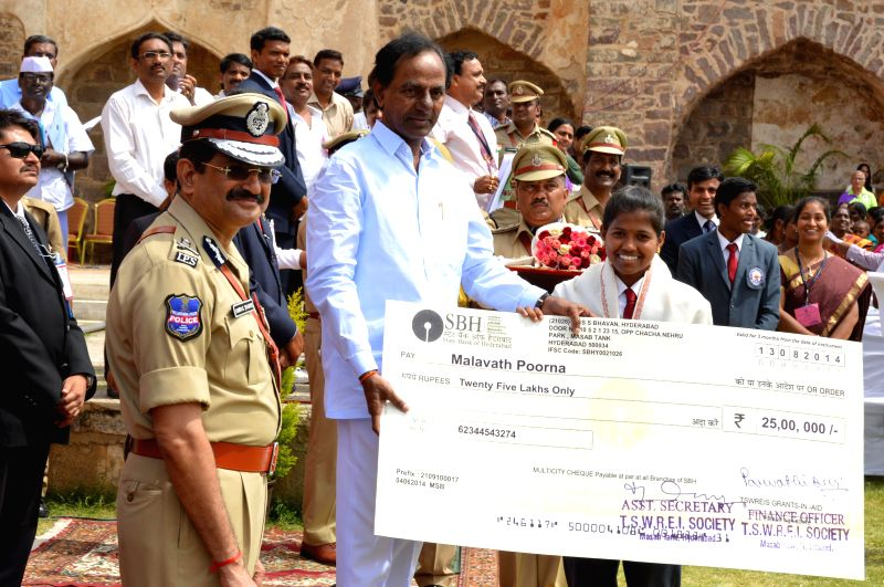 Telangana Chief Minister K Chandrasekhar Rao presents a cheque to Malavath Poorna, who climbed Mount Everest recently during 68th Independence Day celebrations at Golkonda Fort, some 11 km away from . - K Chandrasekhar Rao
