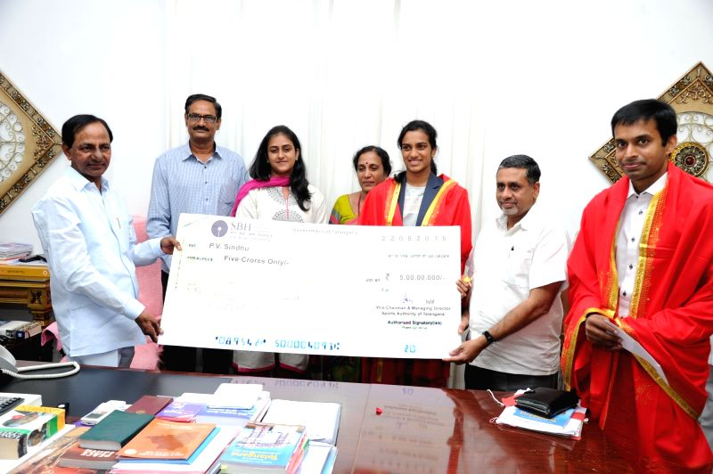 Telangana Chief Minister K Chandrasekhar Rao presents a cheque of Rs Five Crore to Indian badminton player P.V. Sindhu in Hyderabad on Aug 22, 2016. - K Chandrasekhar Rao