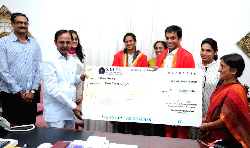 Telangana Chief Minister K Chandrasekhar Rao presents a cheque of Rs One Crore to Indian Badminton team coach Pullela Gopichand in Hyderabad on Aug 22, 2016. - K Chandrasekhar Rao
