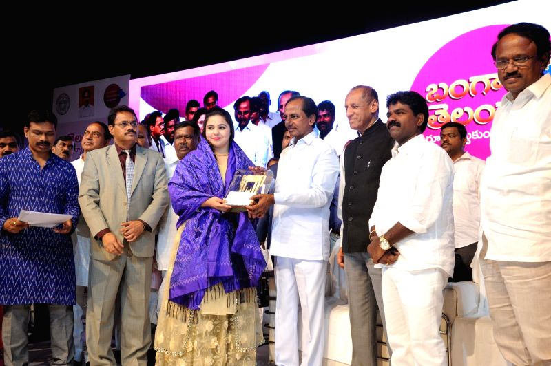 Telangana Chief Minister K Chandrashekar Rao presents award to karate athlete Syeda Falak during a programme organised on the occasion of the state's formation day in Hyderabad on June 2, ... - K Chandrashekar Rao