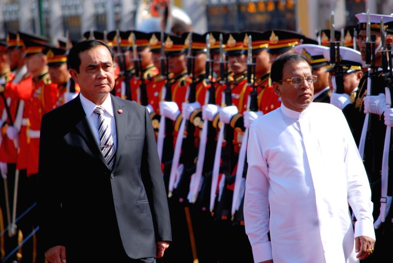 Thai Prime Minister Prayut Chan-o-cha (L) and Sri Lankan President Maithripala Sirisena review an honor guard during a welcoming ceremony at the Government House in ... - Prayut Chan