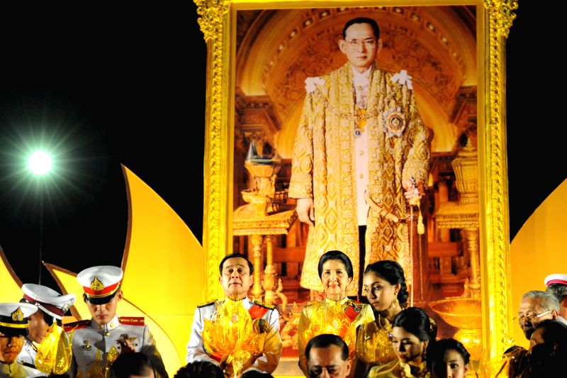 Thai Prime Minister Prayuth Chan-ocha (4th L) lights candles and sings anthems during the celebration of Thai King Bhumibol Adulyadej's 88th birthday in Bangkok Dec. ... - Prayuth Chan