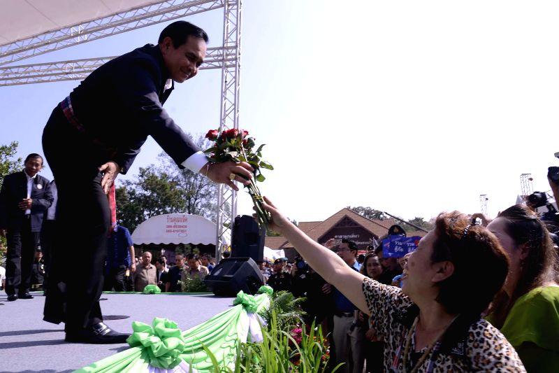 Thailand (Bangkok): Thai prime Minister Gen. Prayuth Chan-ocha (L) is given a bunch of flowers during his visit in Khon Kaen province, Thailand, Nov. 19, 2014. - Gen