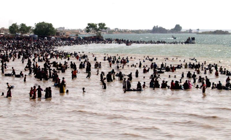 Tourists swim in Keenjhar Lake in southern Pakistan's Thatta on May 12, 2014. Keenjhar Lake is the second largest fresh water lake in Pakistan. It is an important ...