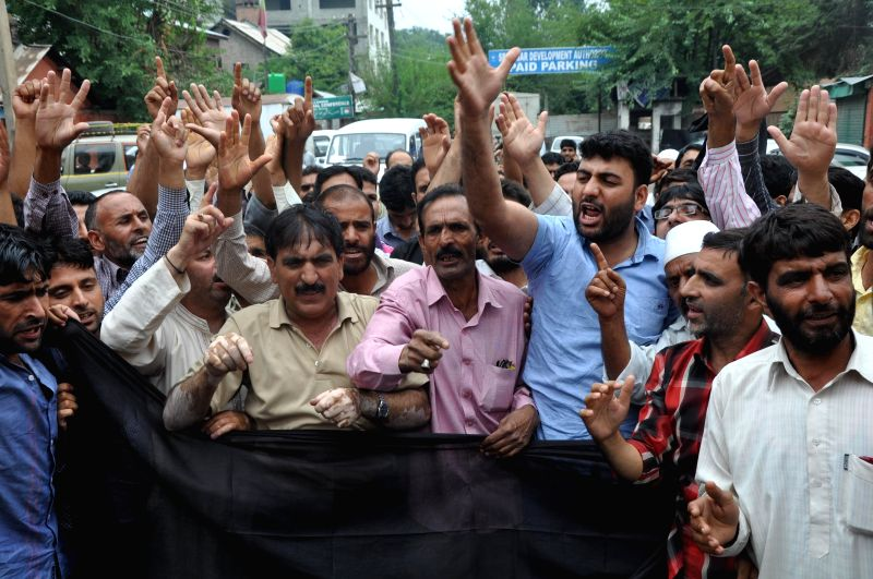 The employees of the department of Public Health Engineering (PHE) demonstrate to press for their demands at Lal Chowk in Srinagar on Aug 8, 2014.