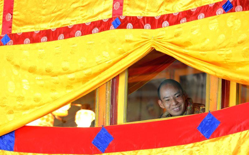 The file photo taken on Sept. 26, 2014 shows the 11th Panchen Lama, Bainqen Erdini Qoigyijabu, watching a cham dance ritual at Tashilhunpo Monastery in Xigaze, ...