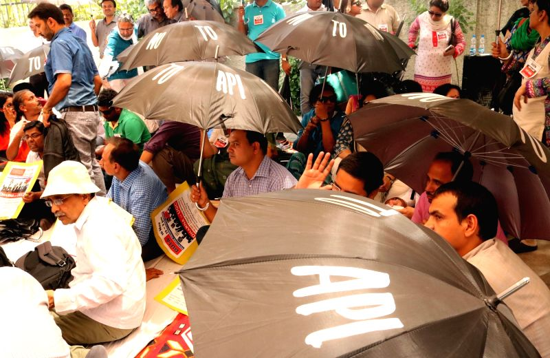 "The members of Delhi University Teachers Association (DUTA) stage an ""umbrella sit-in demonstration"" to press for their demands in New Delhi, on May 16, 2016."