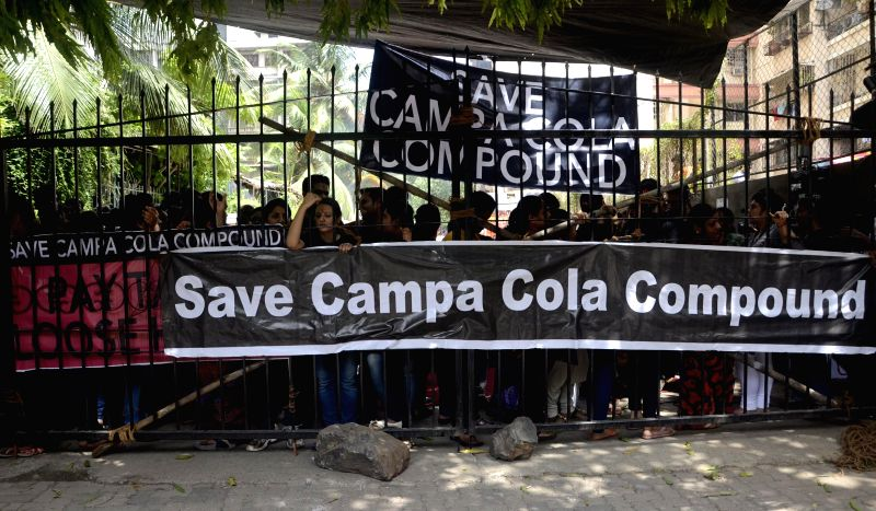 The residents of Worli's Campa Cola Compound form human chains to prevent BMC personnel from entering the compound in Mumbai on June 20, 2014. The BMC personnel had arrived to disconnect water, ...