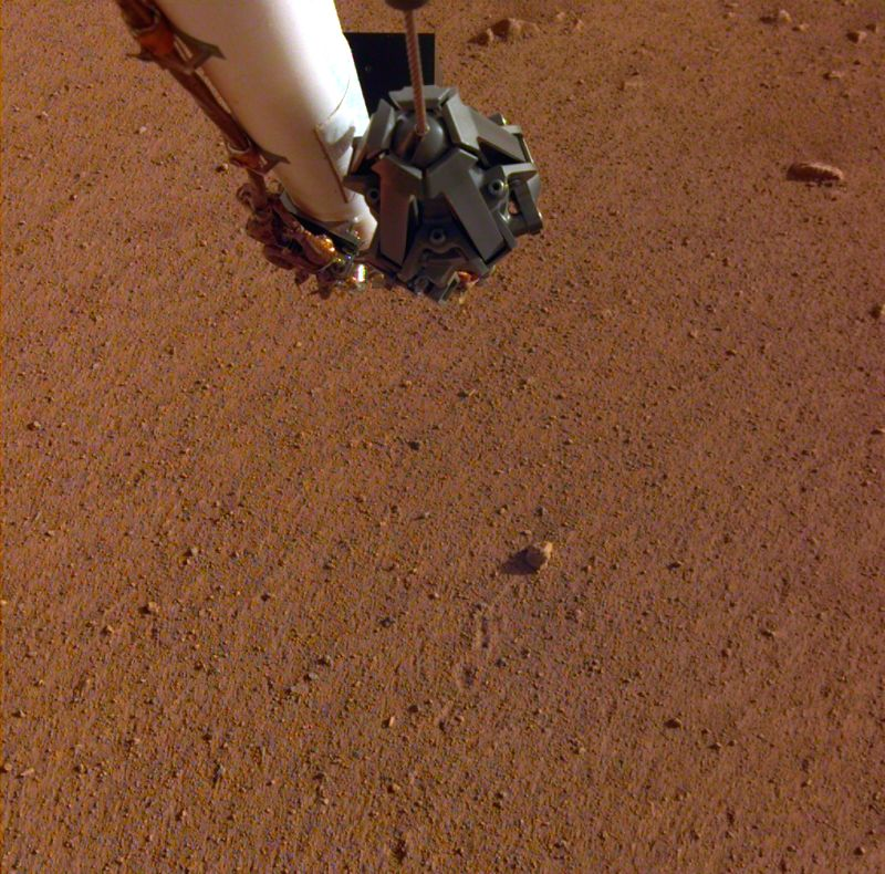 """The rock in the centre of this image was tossed about 3 feet (1 meter) by NASA's InSight spacecraft as it touched down on Mars on November 26, 2018. The rock, which is a little bigger than a golf ball, was later nicknamed """"Rolling Stones Rock"""" in hon"""