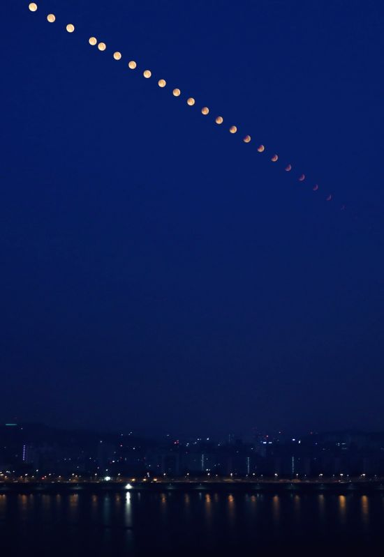 This composite photo captures the moon eclipse in view above Seoul's skyline on July 28, 2018. A photo was taken every five minutes for about two hours starting at 2:13 a.m.