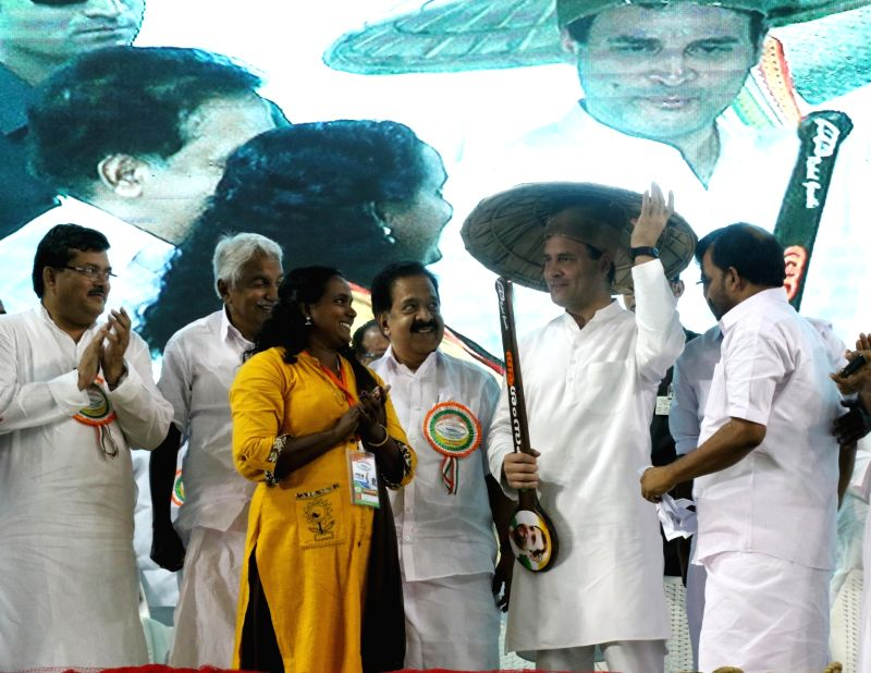 Thrissur: Congress President Rahul Gandhi being welcomed with fishermen's traditional cap 'Pankayam' as he arrives to address the 'Fisherman Parliament' in Thrissur, Kerala on March 14, 2019. Also seen Congress leader Oomen Chandy. (Photo: IANS)(Image Source: IANS News)