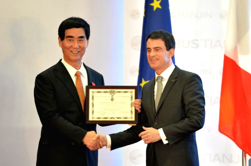 French Prime Minister Manuel Valls (R) presents the Chevalier de la Legion d'Honneur to Mr. Lan Xinguo, former Chairman of Sichuan Airlines, in Tianjin, north ... - Manuel Valls