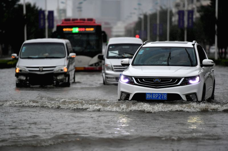 TIANJIN, July 24, 2018 - Cars pass through a flooded road in Nankai District of north China's Tianjin Municipality, July 24, 2018. Heavy downpours brought by Typhoon Ampil pounded Beijing and ...