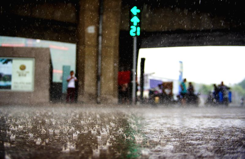 Pedestrians gather under a viaduct for shelter in north China's Tianjin, July 4, 2014. Heavy rainfalls hit the city on Friday.