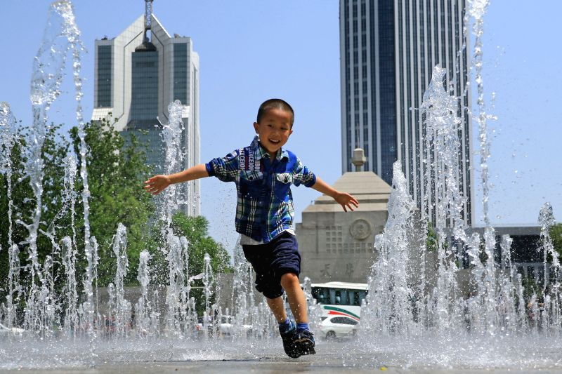 TIANJIN, May 7, 2017 - A child plays in a fountain at Beiyang Square in Tianjin University, in Tianjin, north China, May 6, 2017.