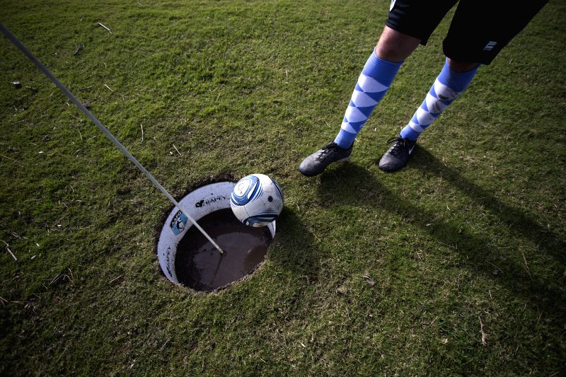 A FootGolf player kicks a ball into a hole during a tournament in a golf field of Tigre, 35 kilometers away from Buenos Aires, capital of Argentina, on May 16, 2014. ..