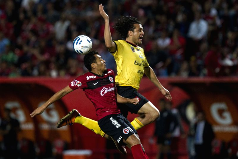Xolos' Juan Arango (L) vies with Leones Negros' Hector Reynoso on day 7 of the Opening Tournament 2014 of the Liga MX soccer match at the Caliente Stadium in ...