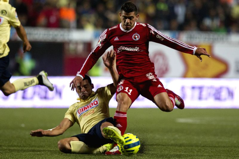 Henry Martin (R) of Xolos vies for the ball with Miguel Samudio (L) of America during a match of MX League's Journey 2 at Caliente Stadium, in Tijuana City, ...