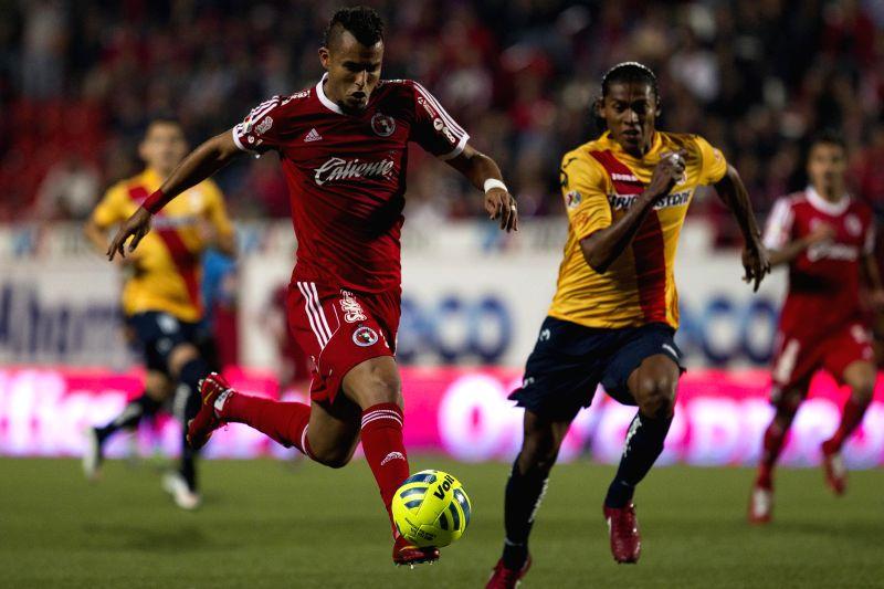 Xolos' Ricardo Da Silva (L) vies with Morelia's Joel Huiqui during a match of the Day 4 of the 2015 Closing Tournament of the MX League in Tijuana city, northwest ..