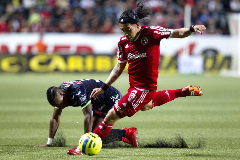Dayro Moreno (R) of Xolos vies for the ball with Leiton Jimenez of Veracruz during a match of Journey 10 of MX League Clousure Tournament 2015 at Caliente Stadium ...