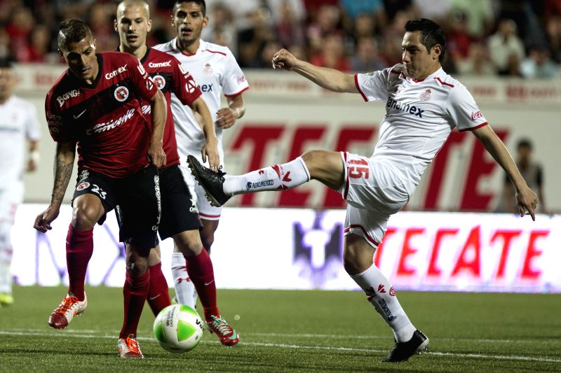 Xolos' Richard Ruiz (1st L) vies for the ball with Antonio Rios (R) of Toluca during their quarterfinals match of the Liga MX, held in the Caliente Stadium, in the ...