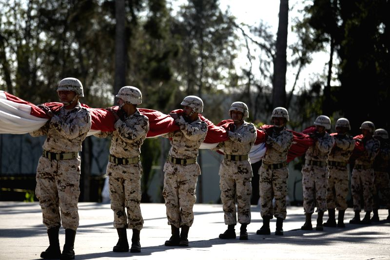 Mexican army soldiers take part in a flag-raising ceremony to kick off the celebrations to mark the Independence Day, in Tijuana city, northeast Mexico, on Sept. 1,