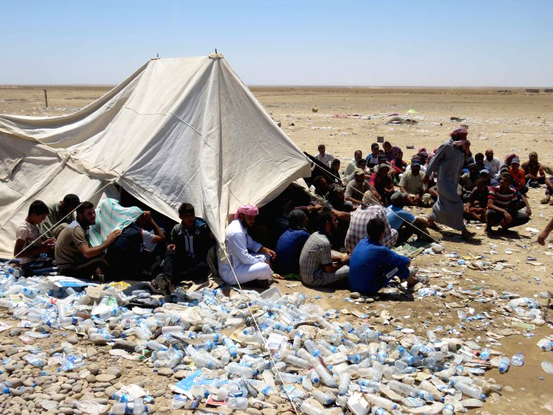 TIKRIT, July 28, 2016 - Displaced people, who fled the Islamic State-held town of Shirqat in Iraq's Salahudin province, sit on the ground after arriving at an Iraqi military base in Hajjaj district, ...