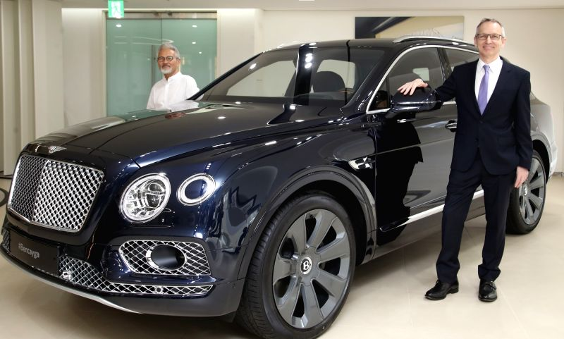 Tim Mackinlay (R), head of Bentley Motors Korea, and South Korean artist Jung Goam pose next to the Bentayga W12 Korean edition by Mulliner at the automaker's showroom in Seoul on July 30, ... - Jung Goam