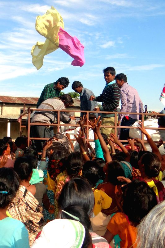 Social workers distribute relief material to people living in a relief camp, at Tinikhuti in Sonitpur district of Assam  on Dec 30, 2014.