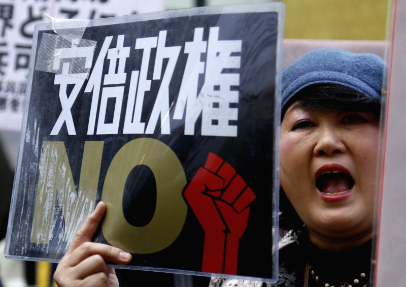 A woman holds a placard during a demonstration to protest against the revision of the pacifist Article 9 of the Japanese Constitution in Tokyo, Japan, April 11, ...