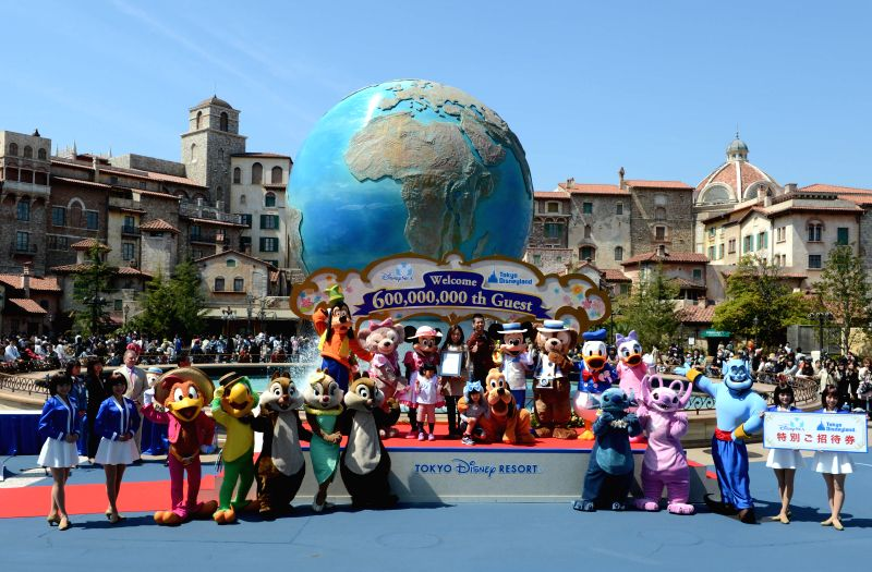 Yumi Sakai (4th L) celebrates with her family and Disney characters as she becomes the 600 millionth guest of Tokyo Disney Resort at the Tokyo DisneySea in Urayasu, .