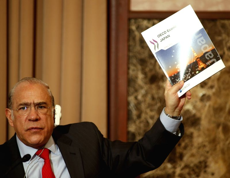 Secretary-General of the Organization for Economic Cooperation and Development (OECD) Angel Gurria shows a survey during a press conference in Tokyo, Japan, April ...