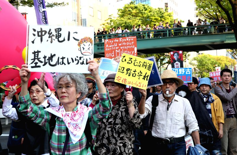 People hold placards and banners during a demonstration against the construction of a new U.S. military base in Okinawa's Henoko, in Tokyo, capital of Japan, on ...