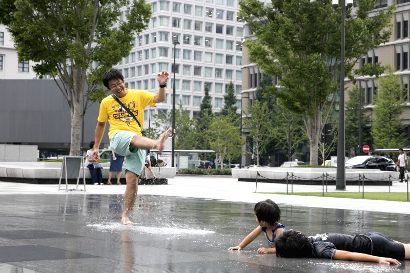 TOKYO, Aug. 3, 2018 - A father and his children cool off in the fountain at Tokyo Station in Tokyo, Japan, on Aug. 3, 2018,