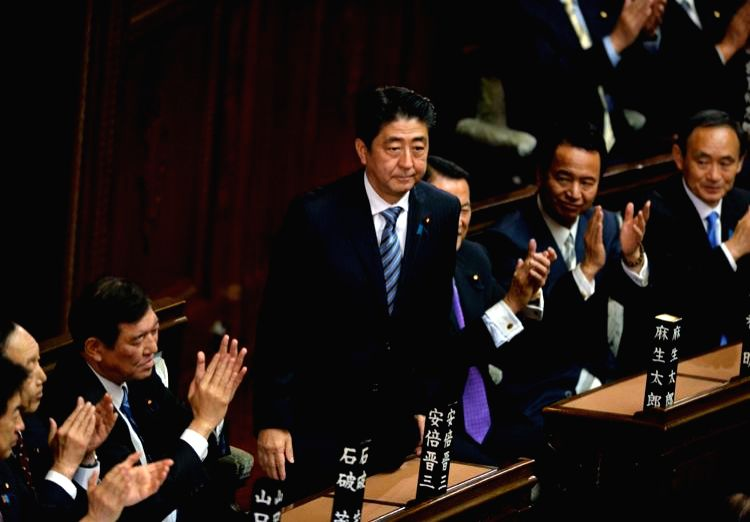 President of Japan's ruling Liberal Democratic Party (LDP) Shinzo Abe (C) greets members of lower house during the meeting at lower house in Tokyo, Japan, Dec. 24, ...