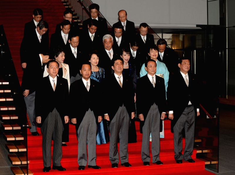 The re-elected Japanese Prime Minister Shinzo Abe (C, 1st row) and his new cabinet pose for a group photo in Tokyo, Japan, Dec. 24, 2014. Japan's top government ... - Shinzo Abe