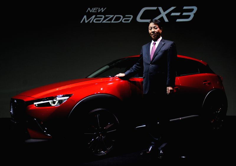 Japan's auto maker Mazda Motor President and CEO Masamichi Kogai poses for photos with a new model of Mazada CX-3 in Tokyo, Japan, Feb. 27, 2015. The model came to ...
