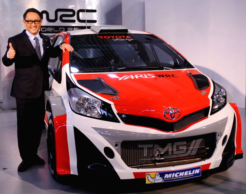"""Toyota's President and CEO Akio Toyoda poses with """"Yaris WRC"""" during a press conference to announce the company's motorsports activities for 2015 in Tokyo, ."""