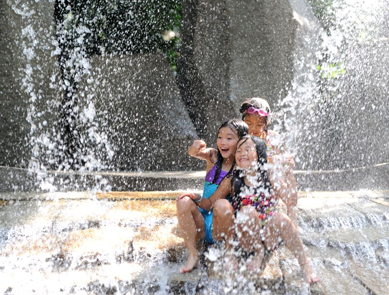 Children play with water at a park in Tokyo, Japan, July 22, 2014. Japan Meteorological Agency announced on Tuesday the end of the rainy season in the Kanto region. ..